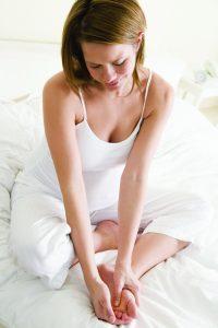 Afbeelding van vrouw die op bed zit met pijnlijke voeten in haar hand